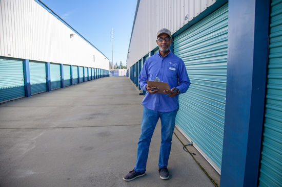 Service representative in front of self storage containers with blue doors