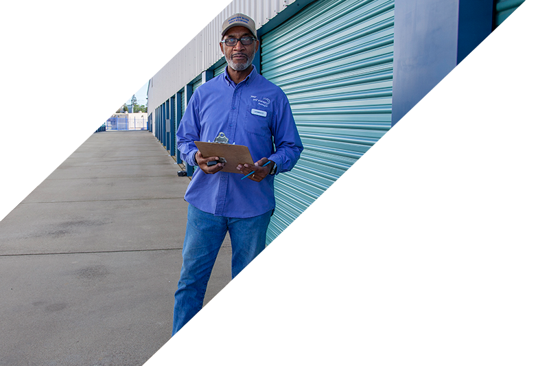 Service Representative in holding clipboard in front of storage containers